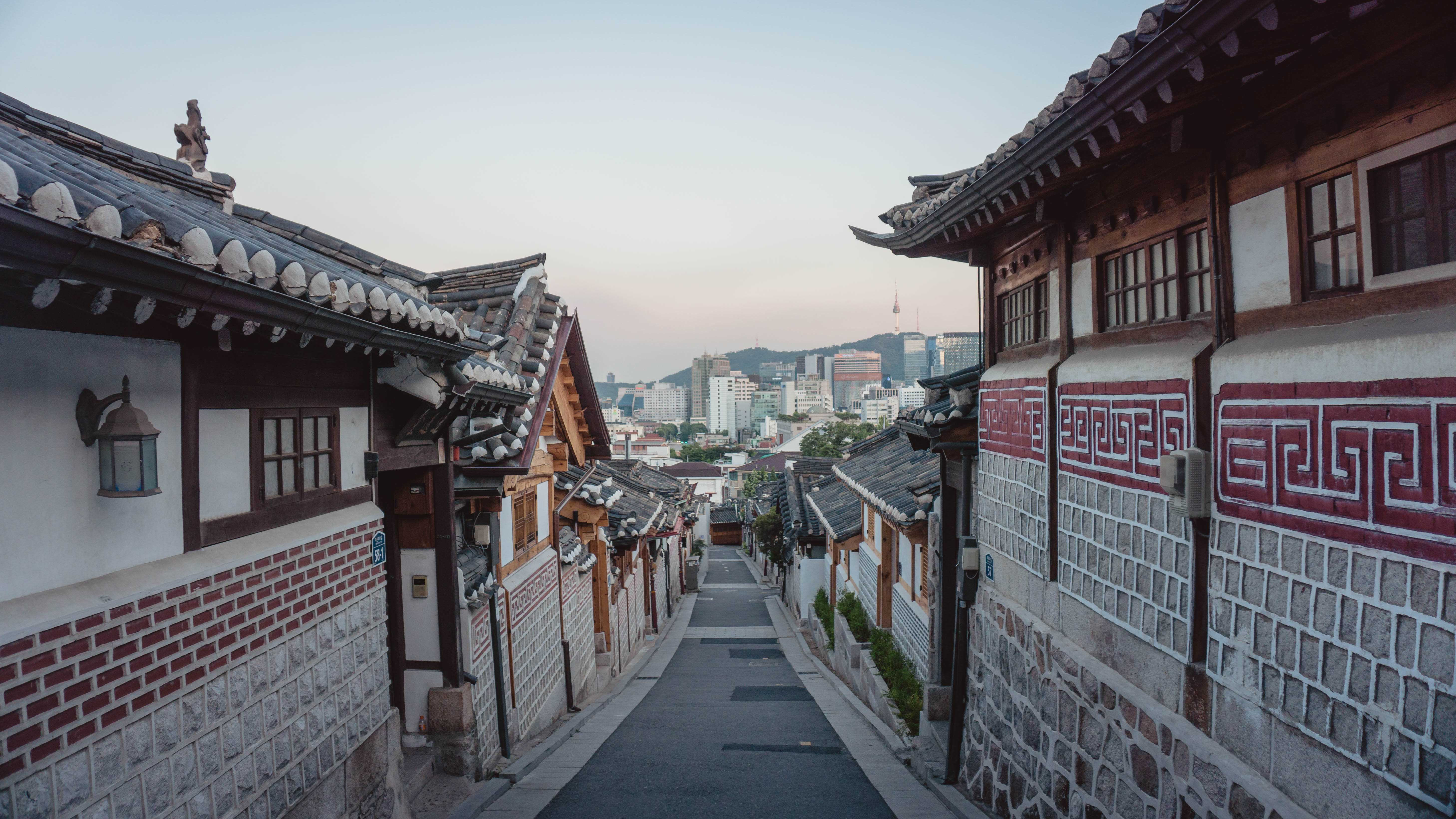 A show of Seoul highrises, taken from between two traditional homes